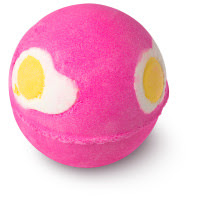 A pink spherical bath bomb with white and yellow circular egg salt shapes on a bright background