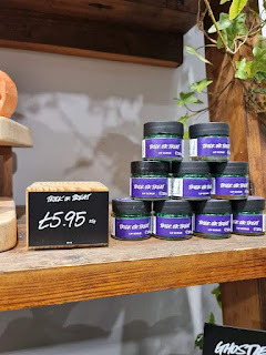 A selection of cylindrical glass jars filled with green sugar with a black circular lid with trick or treat in white font on a light brown rectangular shelf on a bright background