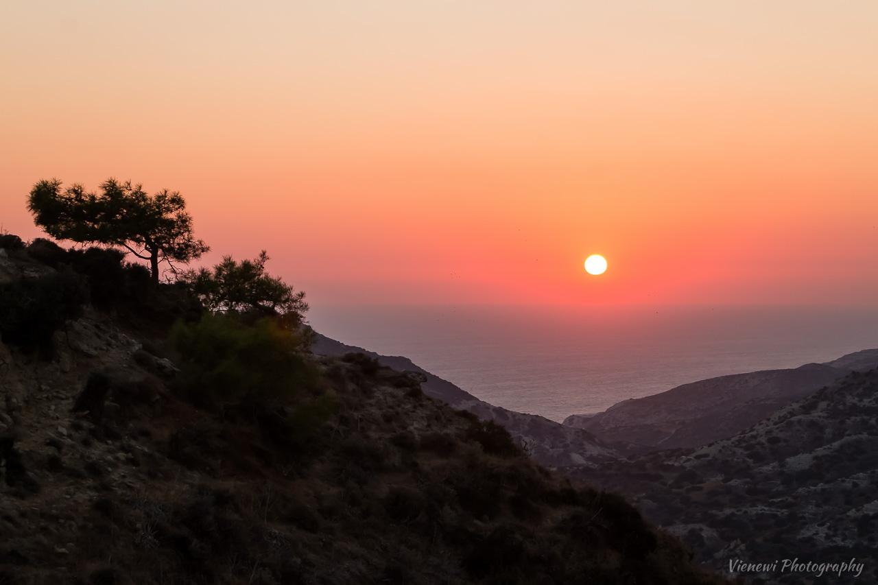 Zachód słońca na szlaku Genesis Aphrodite w okolicach wioski Pissouri. Słońce ponad taflą morza i górzysty krajobraz z sosnami z lewej strony kadru, na wzgórzu.