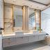 Banheiro neutro com metais dourados, revestido com porcelanato marmorizado + armário clássico!