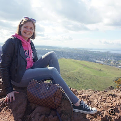 awayfromtheblue Instagram | top of Arthur Seat outfit grey skinny jeans black leather jacket pink tourist hoodie converse