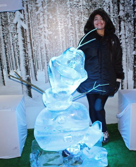 mulher segurando um copo de gelo e olaf de gelo em tamanho real