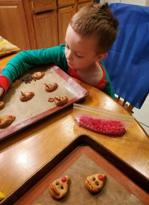 this was an updated photo of making reindeer cookies with my grandson and he is putting antlers on peanut butter cookies shaped into reindeers