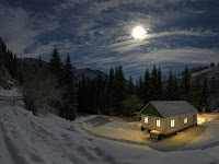 An isolated cottage in a snowy landscape at night with full moon shining