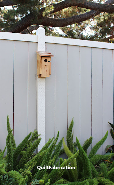 bluebird birdhouse on a fence