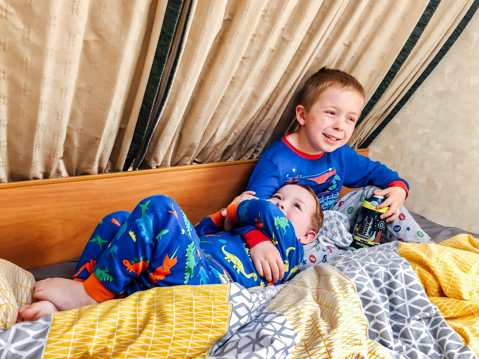 two young boys wearing colourful pyjamas, cuddling and smiling together on a caravan bed