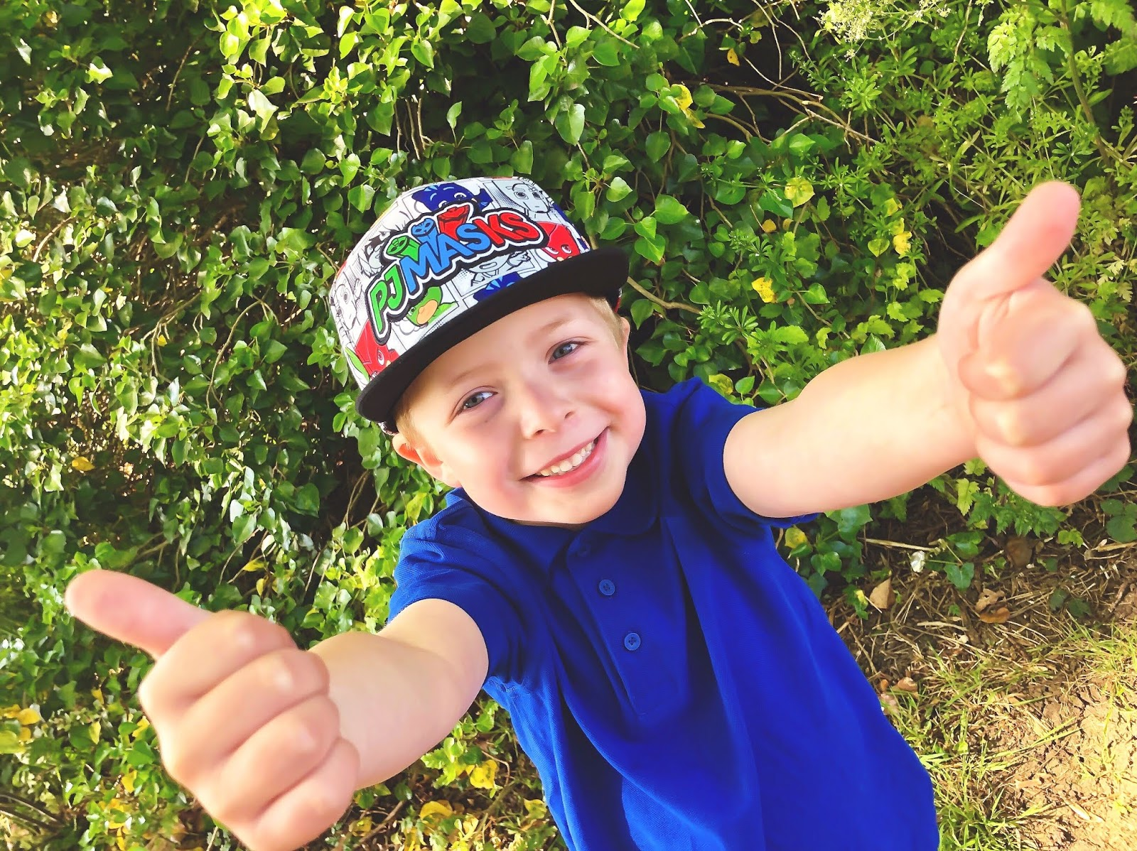 5 year old school boy in blue polo shirt and baseball cap, smiling and giving a thumbs up