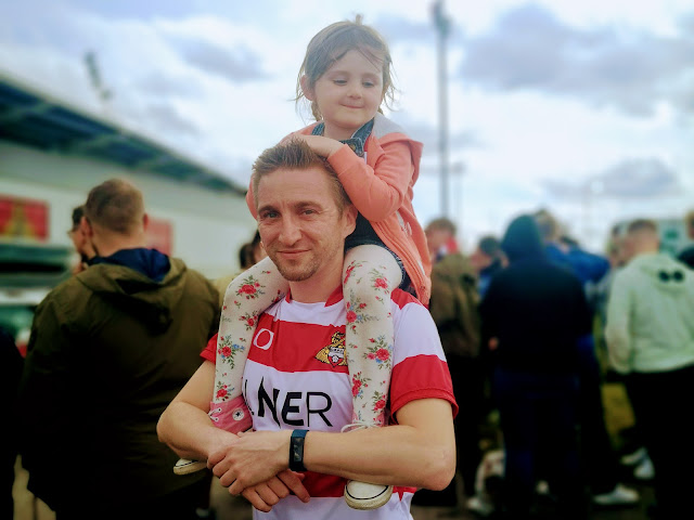 Image of daddy and daughter in matching DRFC football shirts standing outside Doncaster Rovers keepmoat stadium on the day of James Coppingers last game. A small crowd of football fans can be seen in the background.