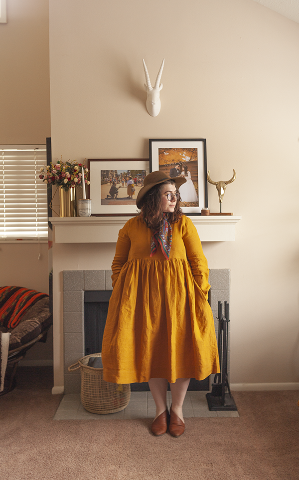 An outfit consisting of an olive brown floppy hat, a warm toned square neck scard tied around the neck, and a yellow linen smock dresses with brown d'orsay flats.