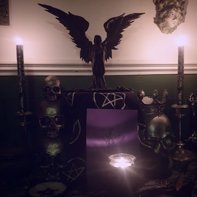 An altar with two silver and black damask candles at either side, a stack of three pewter-coloured resin skulls on the left of the image, a black dish of white salt with a pentagram as part of the stone dish on the left of the image, a life-size silvery resin skull with a crown on the right side of the image. The base altar cloth is silver, grey and black. There is a stand in the middle covered in a black altarcloth with white pentagrams, in front of the stand is a purple card with a sigil on it, and on the stand is a figure of Badb with black out-stretched wings and black robes. At the bottom right of the image, there is a brass-bladed athame dagger with a leaf-shaped blade and a wooden hilt. At the very front of the altar is an ornate black skull-shaped candle-holder containing a grey tealight. All the candles are lit. The altar is in front of a white wall with leaf-green paneling and a white dado rail. The image is candle-lit.