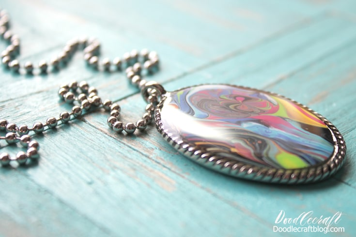 Dirty pour acrylic flo painting art canvas over spill skins turned into stunning pendant bezel jewelry topped with glossy resin.