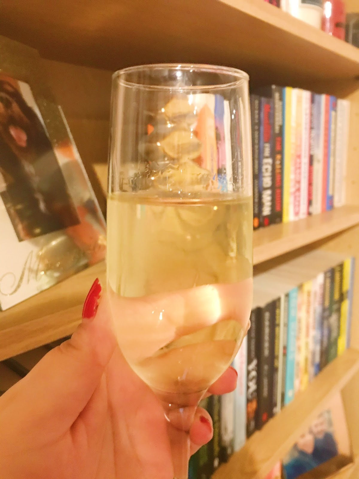 champagne glass held up in front of book case
