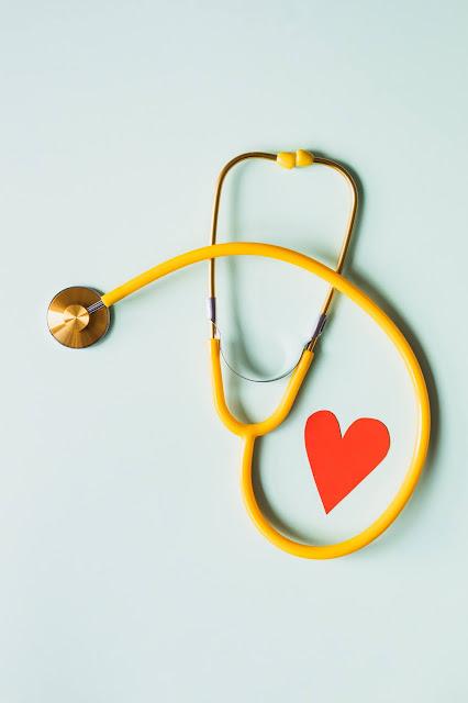 صورة فيها سماعة طبية صفراء اللون بجانبها قلب صغير من الورق باللون الأحمر