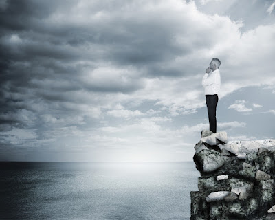 Businessman looking over a cliff to the horizon
