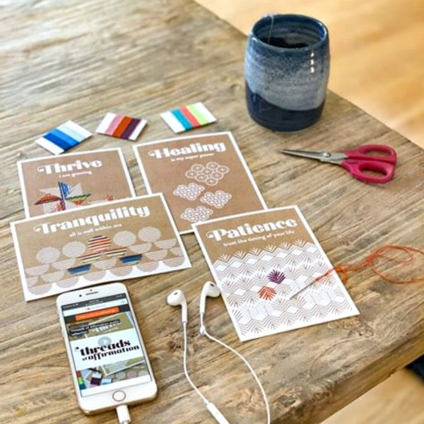 four stitching cards with supplies, phone, and mug on wood table