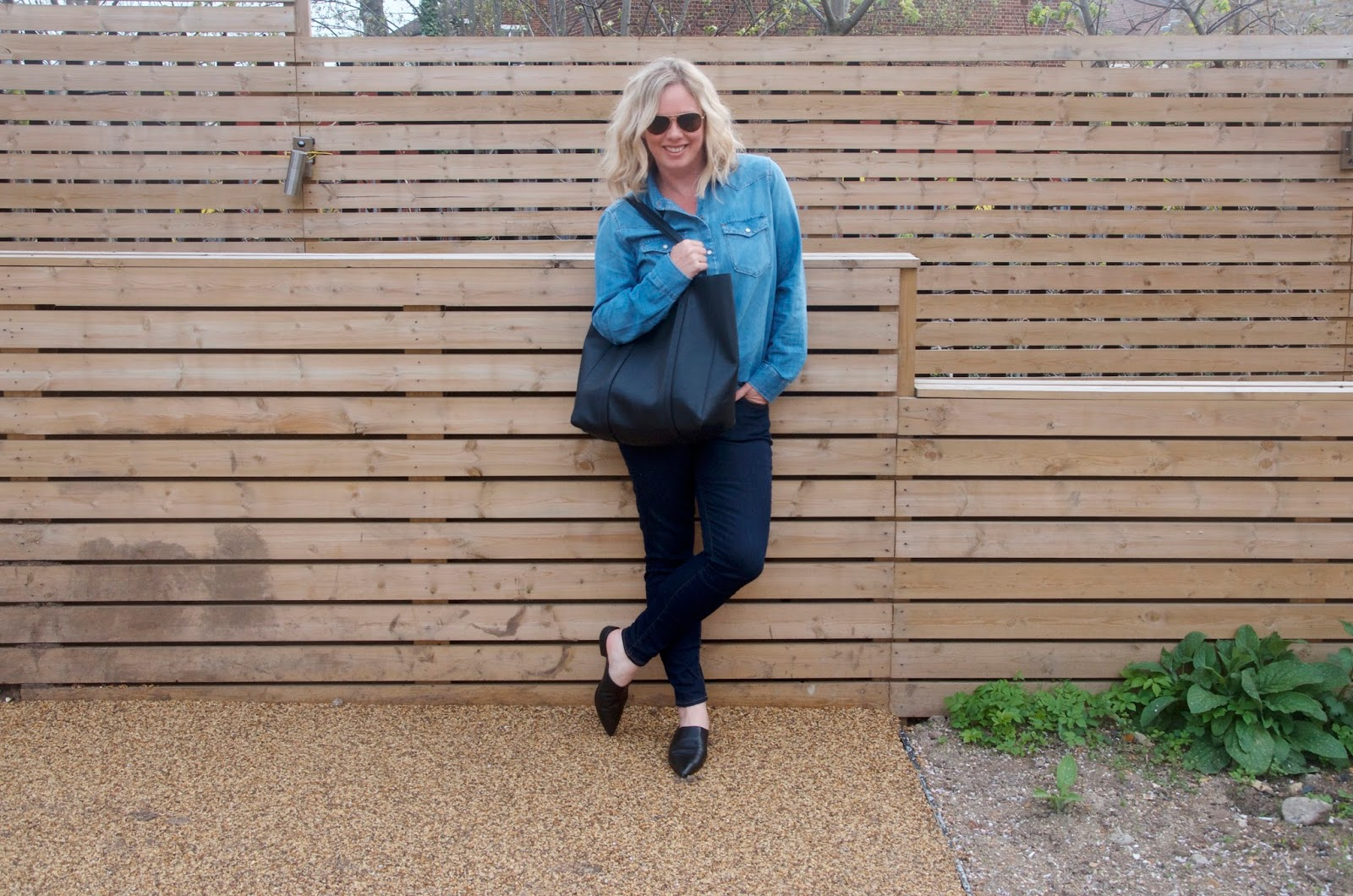 Denim shirt, dark denim jeans, black oversized tote bag, black pointed toe leather mules, gold aviator sunglasses and wooden wall