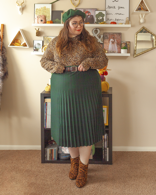 An outfit consisting of a forest green beret, a brown animal print long sleeve top tucked into a forest green pleated midi skit and brown animal print ankle boots.