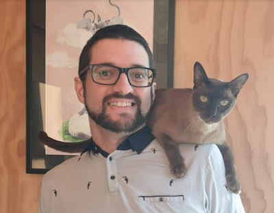 Photo of Rory McCarthy, a person with light skin, glasses, short dark hair,  and a trimmed beard and mustache. A chocolate point Siamese cat is on their shoulder.