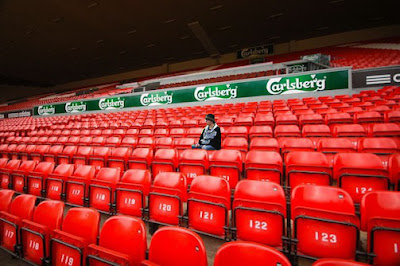 Lonely Liverpool FC fan sitting in Anfield stadium