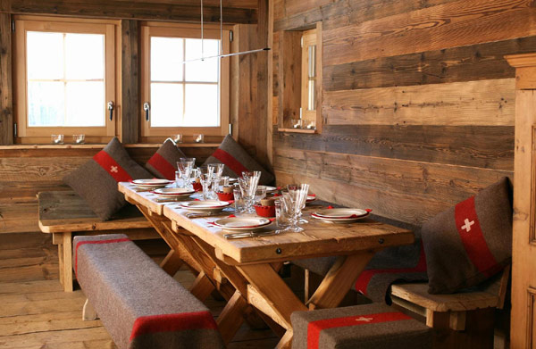 A dining room in a European ski chalet with rustic wood boards on the wall, rustic wood floor, bench style seats around a wood table with red and brown blankets and pillows