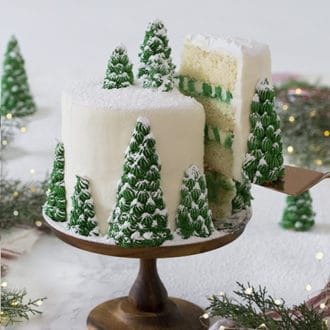 If you saw my Christmas tree cupcakes you know where I got the inspiration for this cake. I cut up a few ice cream cones and used them as the base for various sized pine trees on the side and top of my cake. Little dollops of green buttercream and a dusting of powdered sugar complete the snowy winter scene.