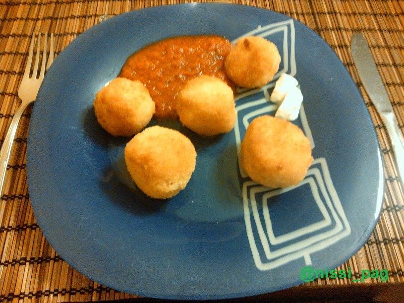 Una ración de croquetas de arroz con salsa de tomate