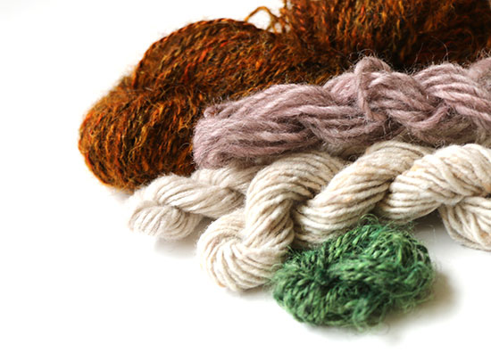 Four skeins of yarn on a white background in dark orange, ivory, rose, and green.