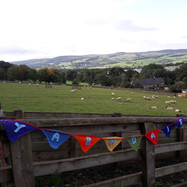 A landscape with hills in the background.  In the foreground is a field with sheep and a crocheted banner spelling out Yarndale hung from the fence