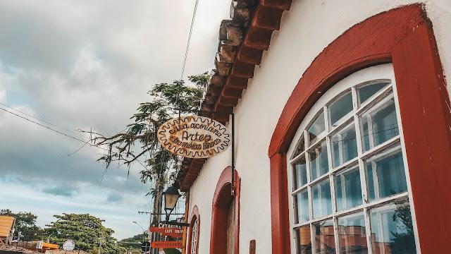 Casa branca, com batentes em vermelho e placa escrito artes