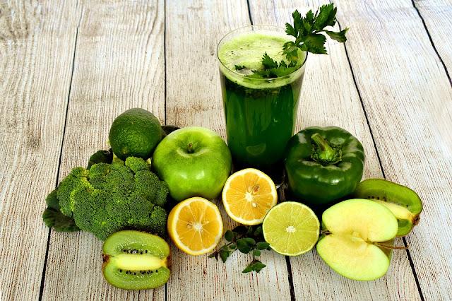 Imagen que muestra batido verde de frutas y vegetales; alrededor vegetales y verduras enteros