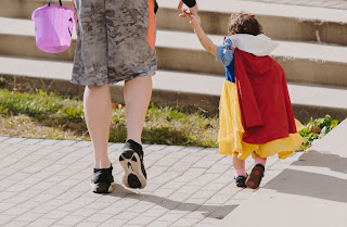 A parent trick or treating with a kid | Hearing aid near Alma MI