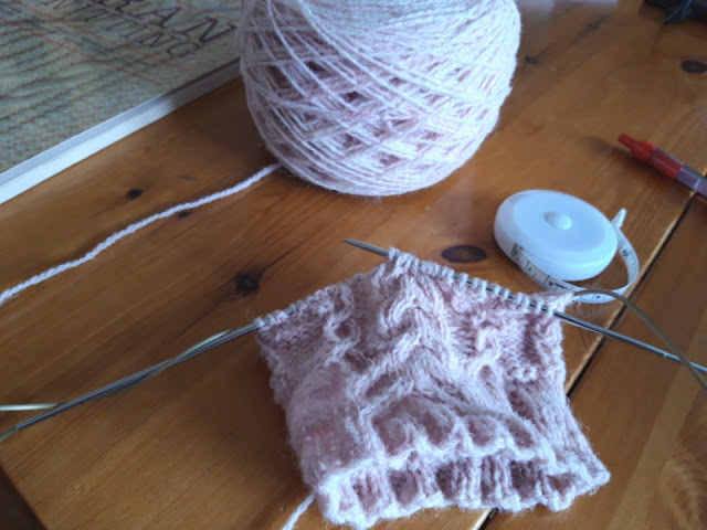 A cake of pink yarn and some test knitting sit on a wooden table.  There is a tape measure and a stitch dictionary on the table