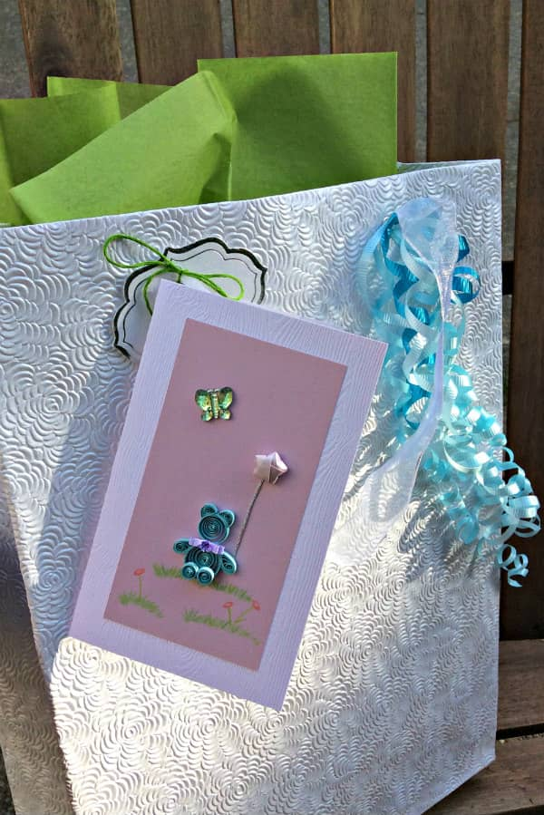 white textured gift bag with handmade quilled bear card and ribbons attached