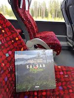 Salsaa & Mojitoa -kirja bussin penkillä, taustalla näkyy bussin ikkunasta vilistävä maisema