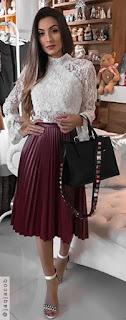 Mulher posando segurando uma bolsa e usando uma sandália branca com pedrarias