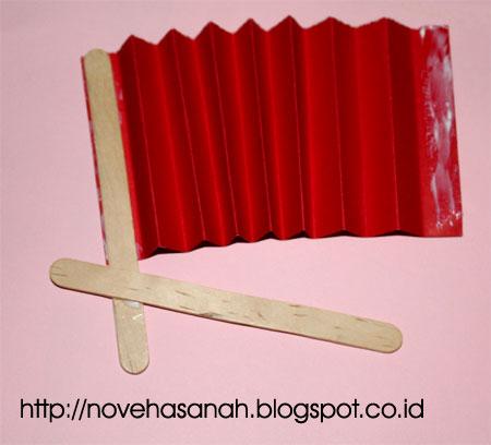 langkah selanjutnya untuk membuat kipas kreasi kertas bekas dan stik es krim adalah dengan melekatkan stik es krim yang telah disilangkan dengan sisi-sisi kertas