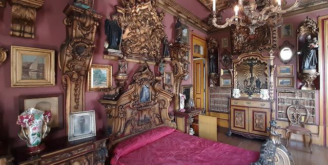 Quarto com cama de casal decorado com madeira em talha dourada