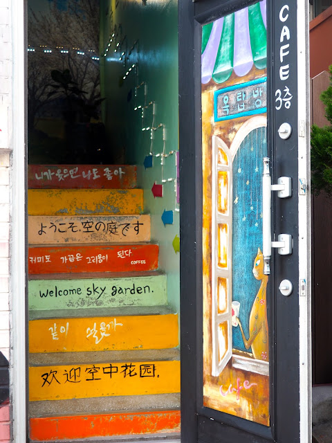 Mural painted on to a door and stairway - cafe entrance in Gamcheon Village, Busan, South Korea
