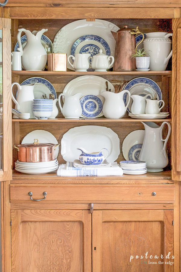 vintage oak hutch with white ironstone and blue and white dishes