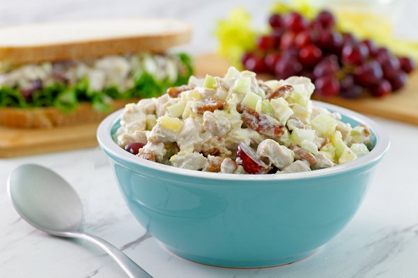 bowl of fruited chicken salad with sandwich in background