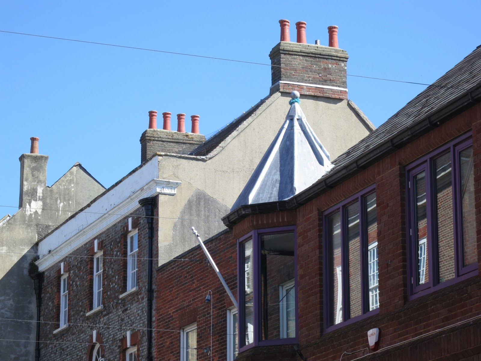 Three sets of chimneys on buildings with windows in Dorchester, Dorset.