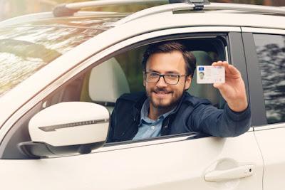 Conductor enseñando su carnet que le permite alquilar y conducir por Islandia