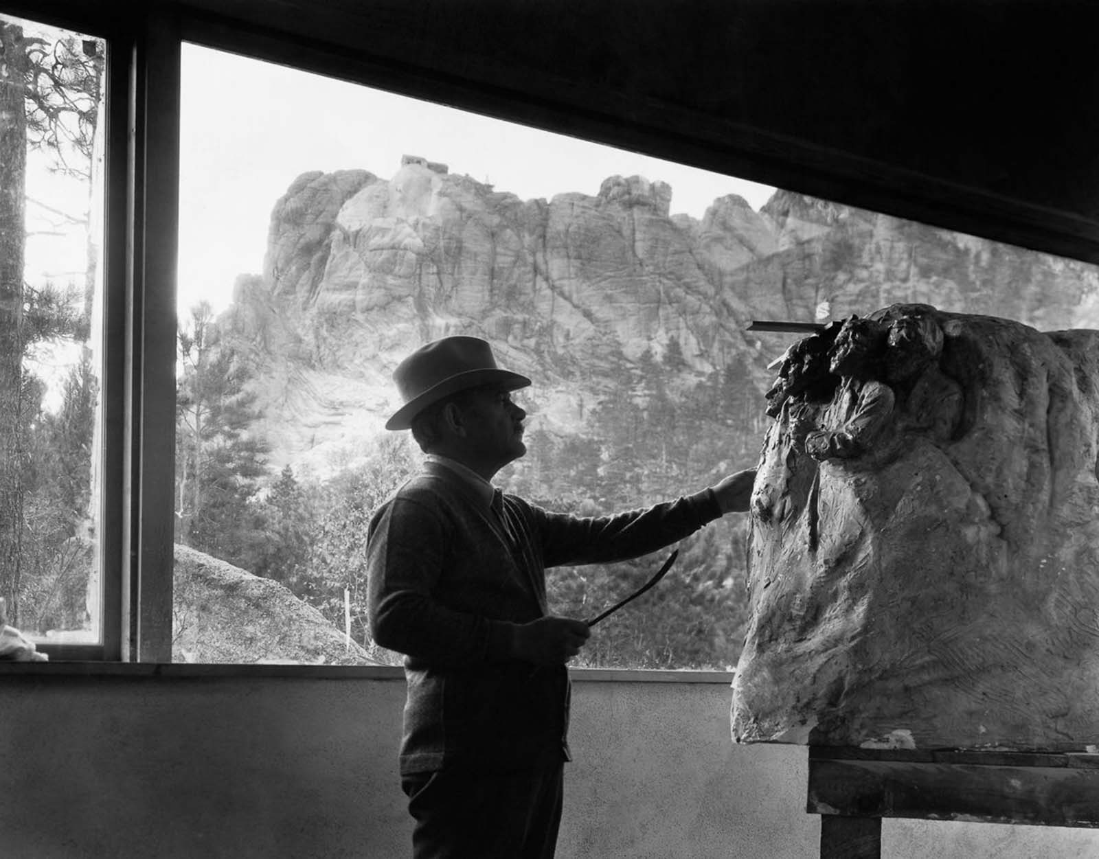 Project leader Gutzon Borglum examines a scale model in his studio below Mount Rushmore. 1930.