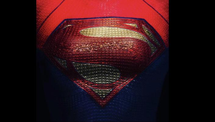 Imagem: o uniforme da Supergirl com a logo no peito. Na parte superior vemos que o uniforme é vermelho, com uma textura de tecido e o símbolo do Superman em formato de diamente em amarelo com um S em vermelho e abaixo azul-escuro e ao redor uma tarja preta.
