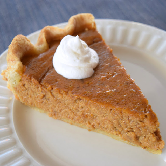 a piece of pumpkin pie with a dollop of whipped cream on a white plate