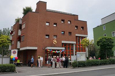 Foto des Myconiushauses in Luzern. Ein Backsteinbau. Im Vordergrund befinden sich ein paar Leute, die zusammenstehen und reden.