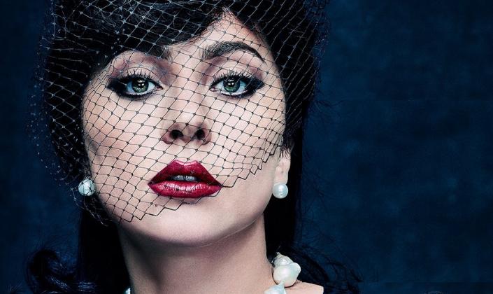 Imagem de capa: um pôster com fundo azul com textura de tecido e com a atriz Lady Gaga, interpretando a personagem Patrizia Reggiani, uma mulher branca, com um véu transparente de viúva, com brincos de pérola, um colar de pedras e roupas pretas.