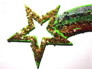 Estrella de belén de cartón hecha por niños y decorada con brillantina.