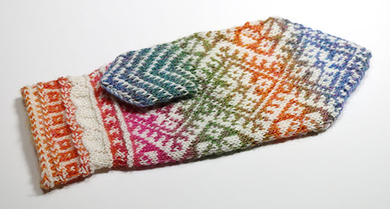 Palm of hand knit wool colorwork mitten showing inner thumb stitches on a white background.