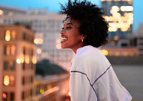 mulher-negra-no-alto-de-um-predio-sorrindo